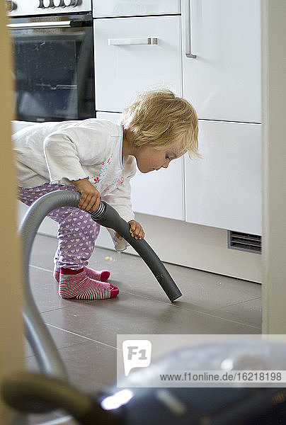 Germany  Kiel  Girl cleaning kitchen with hoover