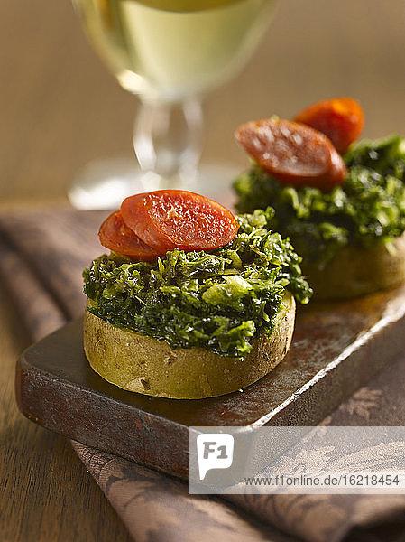 Kartoffelscheiben mit Grünkohl und Wurst  Nahaufnahme