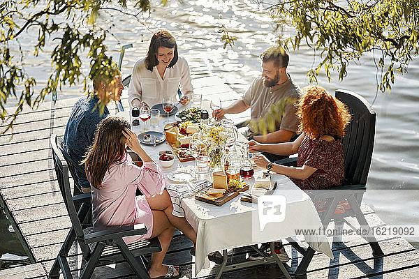 Freunde beim Abendessen am Steg eines Sees Freunde beim Abendessen am Steg eines Sees