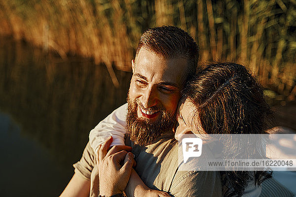 Glückliches  zärtliches Paar  das sich bei Sonnenuntergang an einem See umarmt Glückliches, zärtliches Paar, das sich bei Sonnenuntergang an einem See umarmt