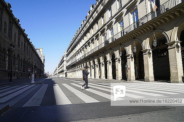 France  Paris 4/04/20 Pedestrian crossing the completely empty rue de Rivoli following the confinement of the population to fight against the COVID-19 pandemic