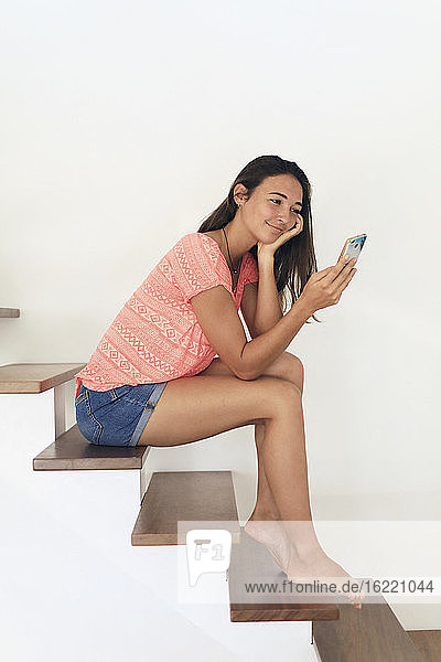 Young teenager at home with a smartphone