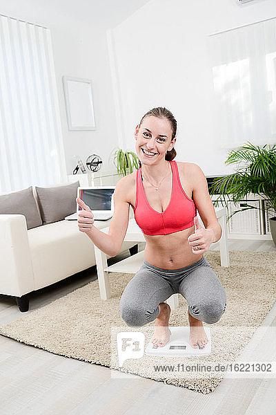 Schöne junge Frau zu Hause mit Gewichtswaage glücklich zu Erfolg Gewichtsverlust Programm.