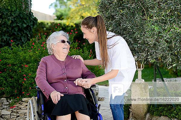 Elderly senior woman on wheelchair with a nurse outdoor in nursing home hospital garden.