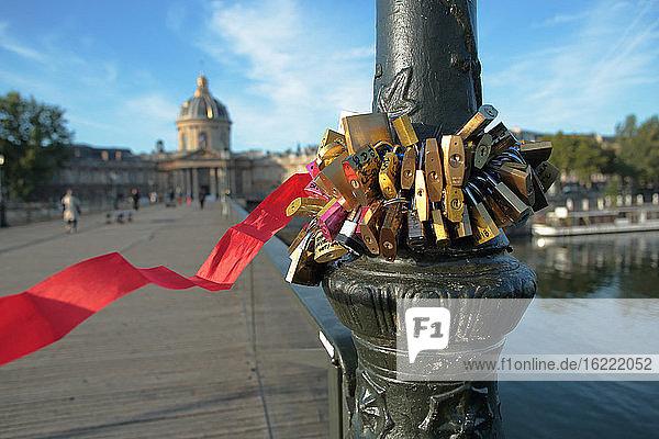 Frankreich  Paris  75  1. Arrondissement  Pont des Arts  Nahaufnahme von Liebesschlössern  die am Fuß eines Laternenpfahls befestigt sind.