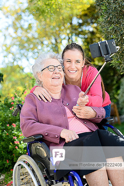 Fröhliche junge Frau macht ein Selfie mit einer älteren Frau in einem Garten eines Seniorenheims.