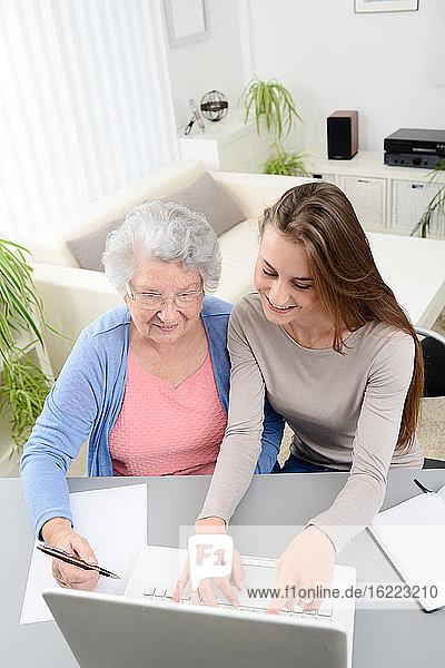 Junge Frau  die einer älteren Frau bei der Erledigung von Papierkram und Verwaltungsverfahren mit einem Laptop zu Hause hilft