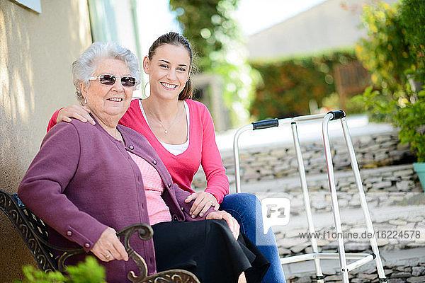 Fröhliche junge Frau im Garten eines Seniorenheims mit einer älteren Dame.