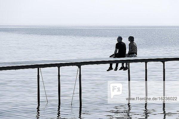 Paar sitzt auf Badesteg  schaut auf das Meer  Uendelige Bro  Unendliche Brücke  Aarhus  Jütland  Dänemark  Europa