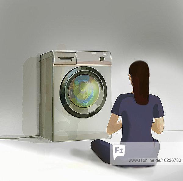 Frau meditiert vor der Waschmaschine