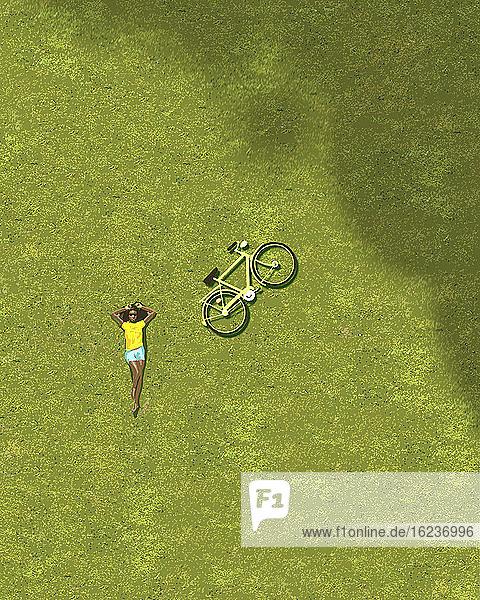 Draufsicht eines Mädchens beim Sonnenbaden auf Gras neben einem Fahrrad