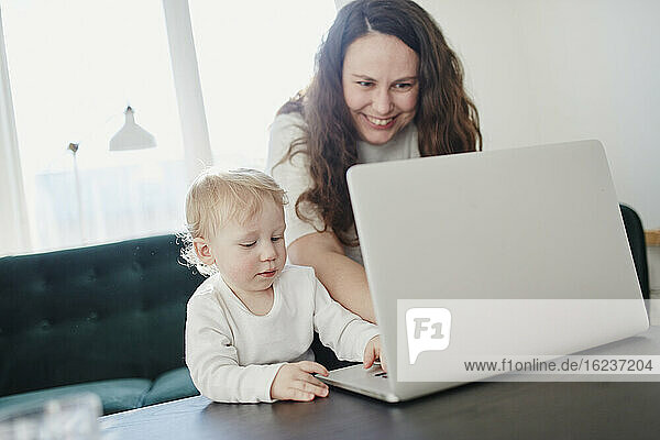 Mother and toddler son using laptop