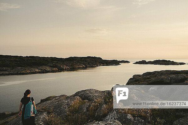 Frau an felsiger Küste bei Sonnenuntergang