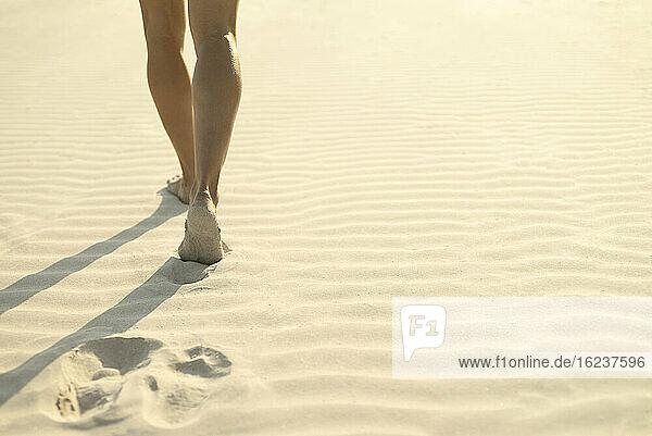 Frau läuft auf Sand