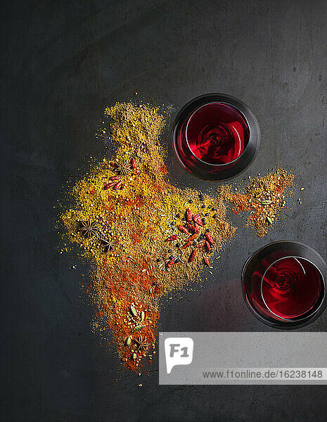 Spices and wineglasses on grey background