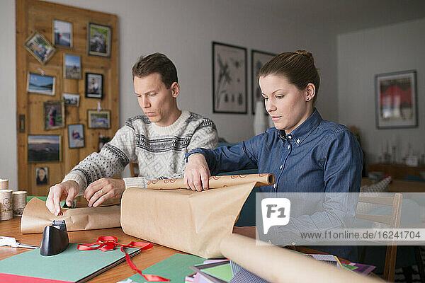 Mildes erwachsenes Paar verpackt Geschenke