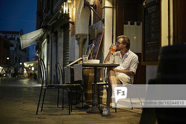 Mann trinkt in einem Straßencafé