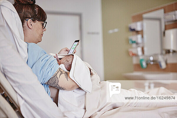 Mother with newborn baby in hospital using phone