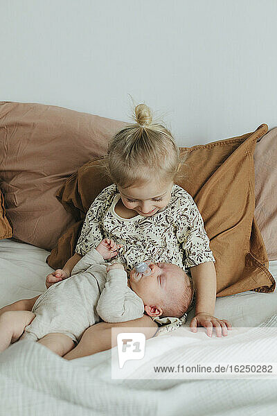 Girl with newborn sibling on bed