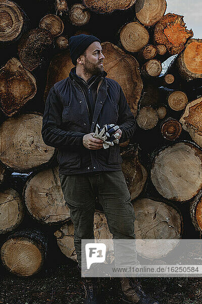 Man standing in front of stack of logs
