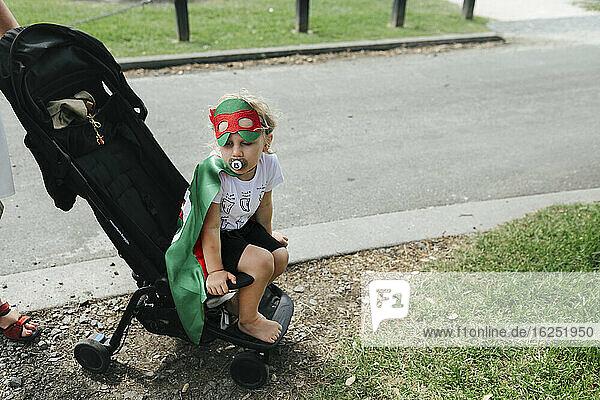 Boy wearing superhero costume sitting in pram