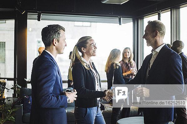 Glückliche männliche und weibliche Kongressteilnehmer schütteln sich die Hände  während sie mit ihrem Amtskollegen stehen