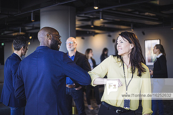 Rückansicht eines männlichen Unternehmers  der einen Kollegen mit Ellbogen im Amt begrüßt