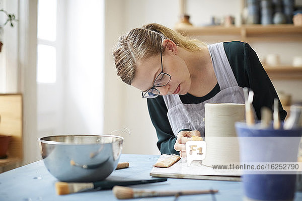 Young woman molding pot in pottery class