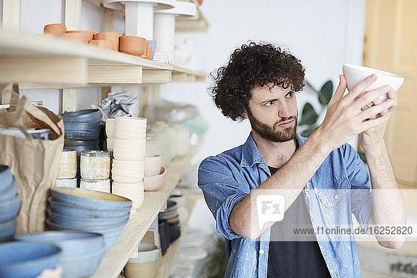 Mittelgroßer erwachsener Mann untersucht Schale in der Töpferklasse