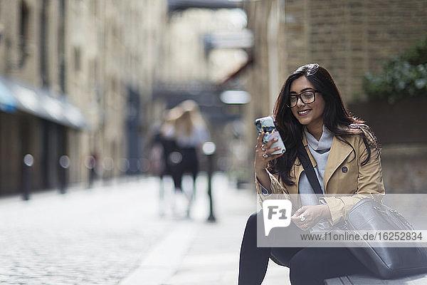Lächelnde Geschäftsfrau mit Smartphone auf dem Bürgersteig der Stadt