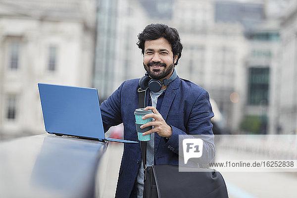 Porträt eines lächelnden Geschäftsmannes mit Laptop und Kaffee auf der Stadtbrücke