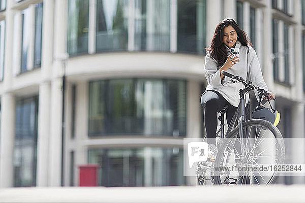 Lächelnde Frau mit Smartphone auf dem Fahrrad in sonniger Stadt