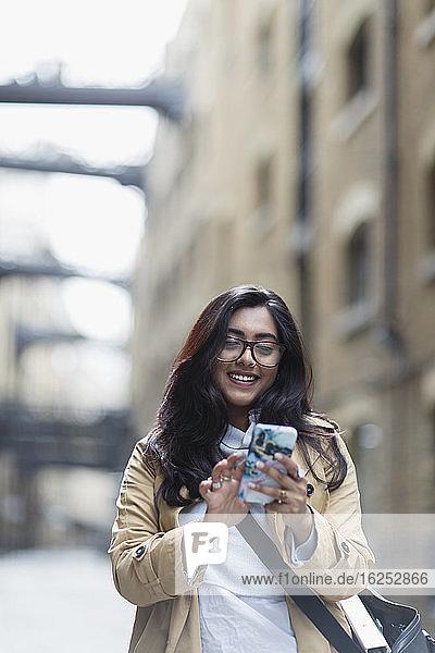Lächelnde Frau mit Smartphone auf dem Bürgersteig