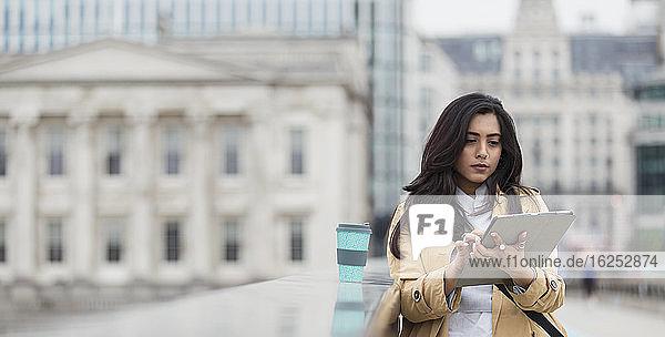 Geschäftsfrau benutzt digitales Tablett auf der Stadtbrücke