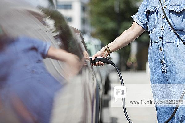Frau  die ein Elektroauto auflädt