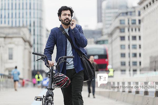 Geschäftsmann mit Fahrrad spricht mit Smartphone auf der Stadtbrücke