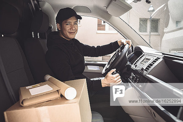 Portrait of male driver with package sitting in truck