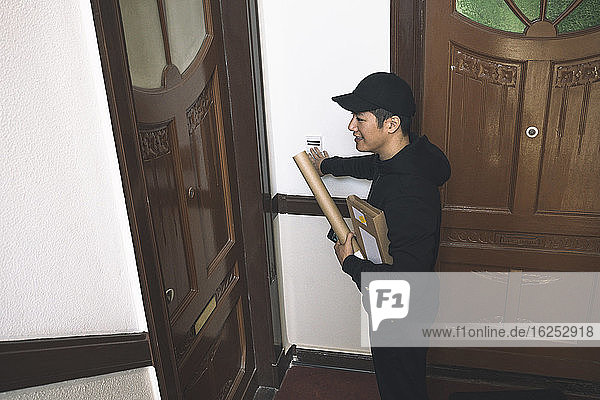 High angle view of smiling delivery man with package at doorstep