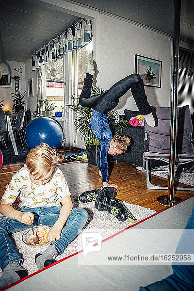 Girl balancing on hand while brother eating in living room