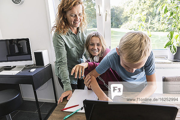 Smiling mother and sister looking at male teenager using laptop