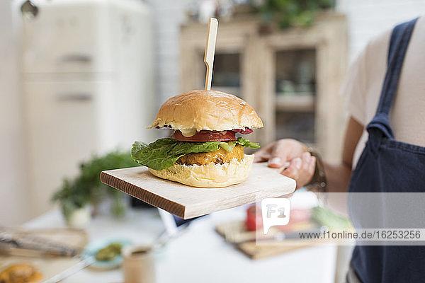 Nahaufnahme einer Frau  die einen Cheeseburger auf einem Schneidebrett hält