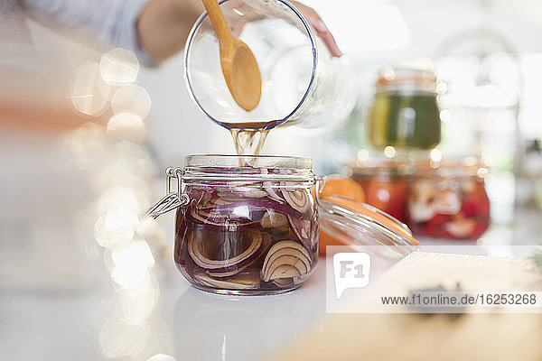 Woman pickling red onions in jar