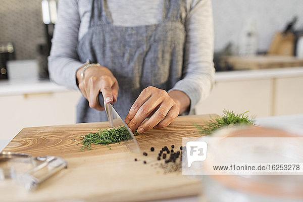 Frau schneidet frische Kräuter auf Schneidebrett in der Küche