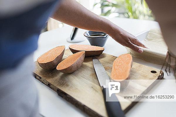Frau schneidet Süßkartoffeln auf Schneidebrett in der Küche