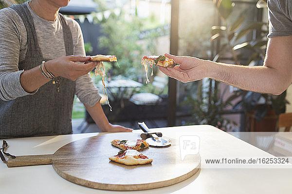 Ehepaar genießt hausgemachte Pizza am Esstisch
