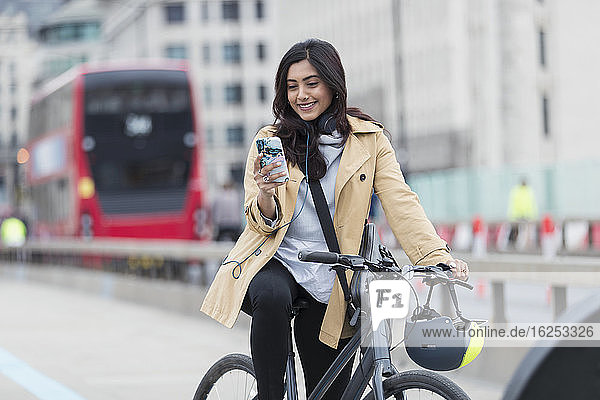 Smiling businesswoman using smart phone on bicycle in city  London  UK