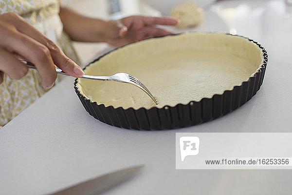 Nahaufnahme einer Frau  die mit einer Gabel Löcher in die Tortenkruste sticht