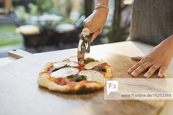 Frau schneidet frische hausgemachte Pizza mit dem Slicer