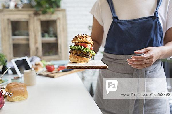 Frau serviert Hamburger auf Schneidebrett in der Küche