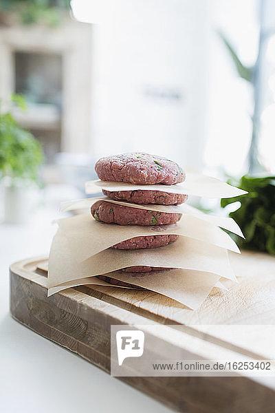 Rohe Hamburger-Frikadellen zwischen Pergamentpapier gestapelt